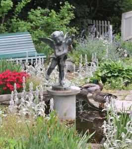 A cherub statue holding a dolphin on a pedestal in a pond