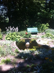 a pot of flowers on a pedestal in the garden in Eldon House, with a green bench in the background