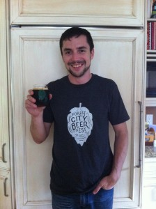 """Founder of the Forest City Beer Fest, Aaron Brown, holding a glass of beer with """"Forest City Beer Fest"""" on the a green outline of a leaf. His navy t-shirt also has the logo, but the leaf is filled in white."""