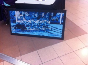 A blue painting of rowers, for Western's Para-rowing team