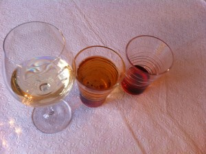 A glass of white wine, a glass of beer and a glass with red sourpuss