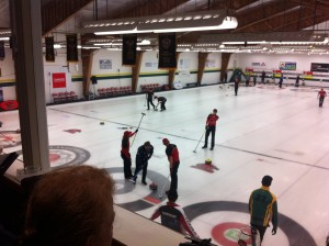 The Fanshawe Men's Curling team on the ice, with NAIT. Person is watching from the balcony