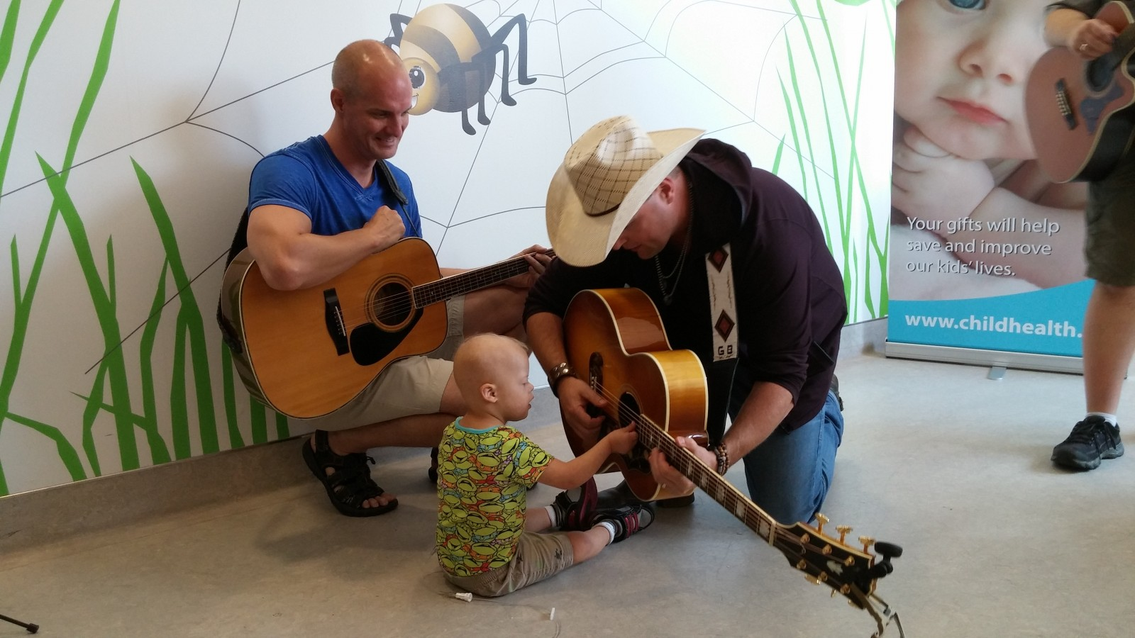 Young patient of the LHSC takes a special interest in Bamford's guitar.